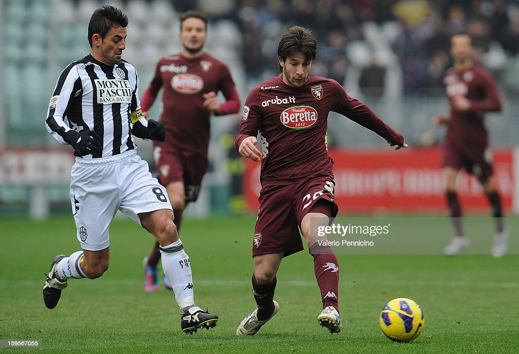 Gianluca Sansone (R) of Torino FC in action against Simone Vergassola of AC Siena during the Serie A match between Torino FC and AC Siena at Stadio Olimpico di Torino on January 13, 2013 in Turin, Italy.