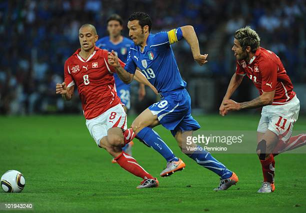 Gianluca Zambrotta of Italy battles for the ball with Gokhan Inler and Valon Behrami of Switzerland during the international friendly match between...