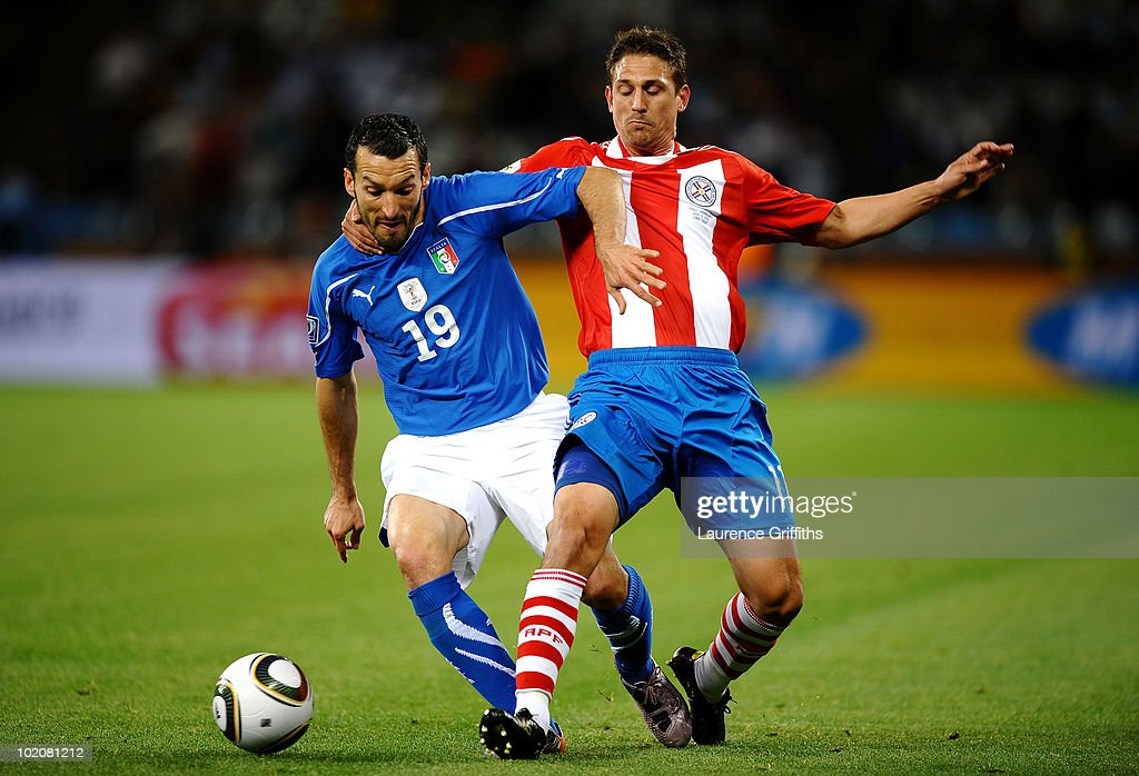 Gianluca Zambrotta of Italy tangles with Jonathan Santana of Paraguay during the 2010 FIFA World Cup South Africa Group F match between Italy and Paraguay at Green Point Stadium on June 14, 2010 in Cape Town, South Africa.