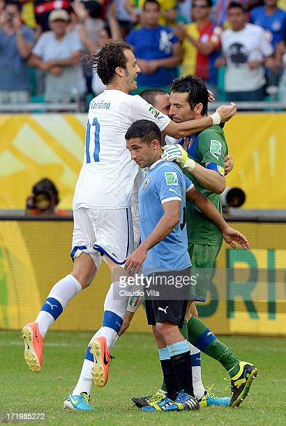 Gianluigi Buffon of Italy celebrates with his teammates after saving the penalty of Walter Gargano of Uruguay to clinch victory in a shootout during...