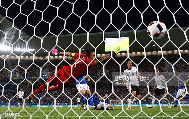 Gianluigi Buffon of Italy dives in vain as Mesut Oezil of Germany scores the oepning goal during the UEFA EURO 2016 quarter final match between...