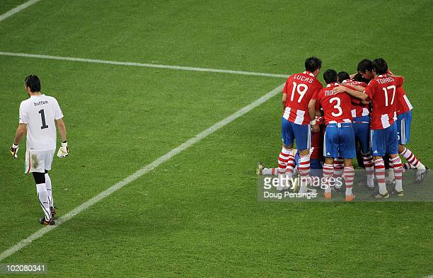 Gianluigi Buffon of Italy walks away dejected as the Paraguay players celebrate after Antolin Alcaraz of Paraguay scores the opening goal during the...
