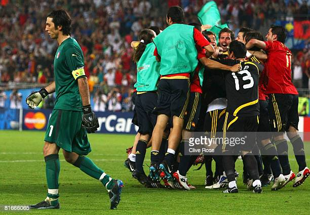 Gianluigi Buffon of Italy walks off dejected as Spanish players celebrate after Cesc Fabregas of Spain shoots and scores the winning penalty in the...