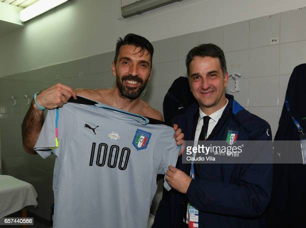 Gianluigi Buffon of Italy with a team jersey celebrating his 1000 career appearances with CEO of Italian Football Association Michele Uva after the...