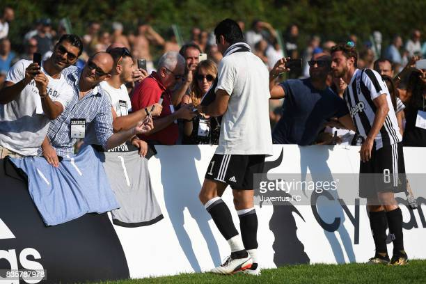 Gianluigi Buffon of Juventus A signs autographs for fans during the preseason friendly match between Juventus A and Juventus B on August 17 2017 in...