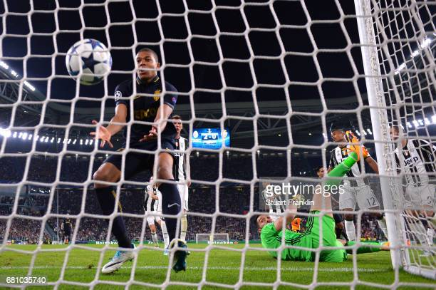 Gianluigi Buffon of Juventus looks back as Kylian Mbappe of AS Monaco picks the ball out of the net after he scores his sides first goal during the...