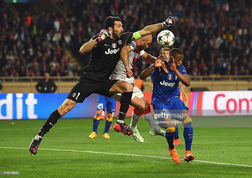 Gianluigi Buffon of Juventus punches clear as Patrice Evra of Juventus takes evasive action during the UEFA Champions League quarterfinal second leg...