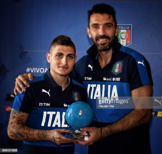 Gianluigi Buffon receives the Pallone Azzurro trophy from Marco Verratti at Coverciano on March 26 2017 in Florence Italy