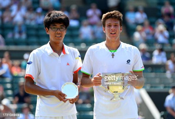 Gianluigi Quinzi of Italy and Hyeon Chung of Korea pose with their trophies after their Boys' Singles Final match on day thirteen of the Wimbledon...