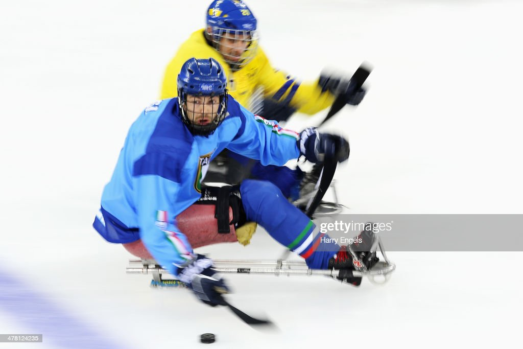 Gianluigi Rosa of Italy is chased by Marcus Holm of Sweden during the Ice Sledge Hockey Classification match between Italy and Sweden at the Shayba Arena during day five of the 2014 Paralympic Winter Games on March 12, 2014 in Sochi, Russia.