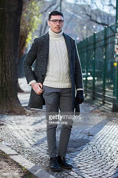 Gianmarco Depretisia wears a dark checkered coat with a white knit turtleneck sweater and gray trousers during the Milan Men's Fashion Week...