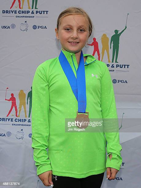 Gianna Papa overall competition first place winner poses with her medal in the Girls 79 group during the 2015 Drive Chip and Putt Championship at The...