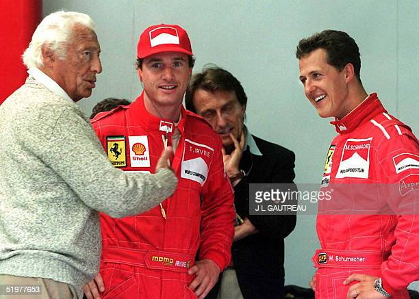 Gianni Agnelli the chairman of Fiat talks to Ferrari Formula One team drivers Eddie Irvine of Ireland and Michael Schumacher of Germany at the...
