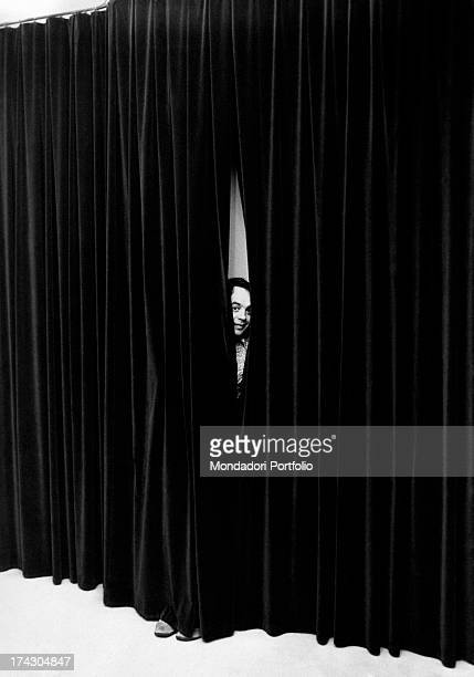 Gianni Boncompagni the radio broadcaster and television writer emerges with his head from behind a curtain the broadcaster is experiencing great...