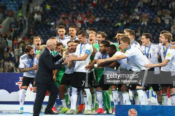 Gianni Infantino FIFA president hands Julian Draxler of Germany the trophy after the FIFA Confederations Cup Russia 2017 Final between Chile and...