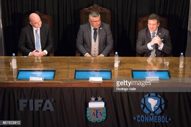 Gianni Infantino president of FIFA Claudio Chiqui Tapia president of AFA and Alejandro Dominguez of CONMEBOL pose during a press conference at AFA as...