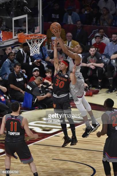 Giannis Antetokounmpo of the Eastern Conference dunks the ball against Stephen Curry of the Western Conference during the NBA AllStar Game as a part...
