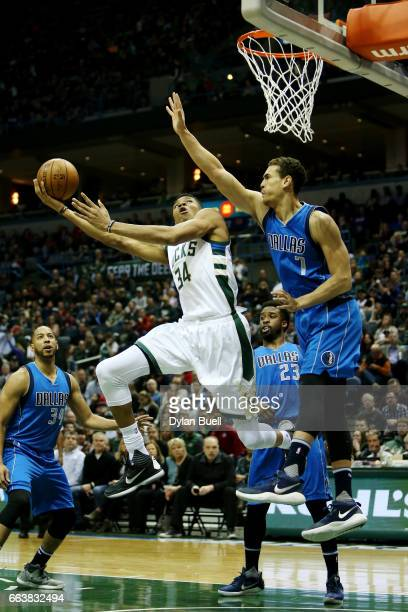 Giannis Antetokounmpo of the Milwaukee Bucks attempts a layup while being guarded by Dwight Powell of the Dallas Mavericks in the second quarter at...