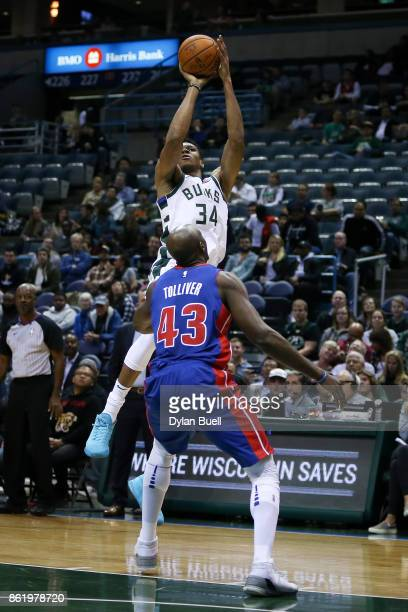 Giannis Antetokounmpo of the Milwaukee Bucks attempts a shot over Anthony Tolliver of the Detroit Pistons in the first quarter during a preseason...
