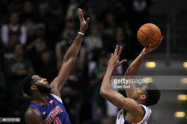 Giannis Antetokounmpo of the Milwaukee Bucks attempts a shot while being guarded by Andre Drummond of the Detroit Pistons in the third quarter during...