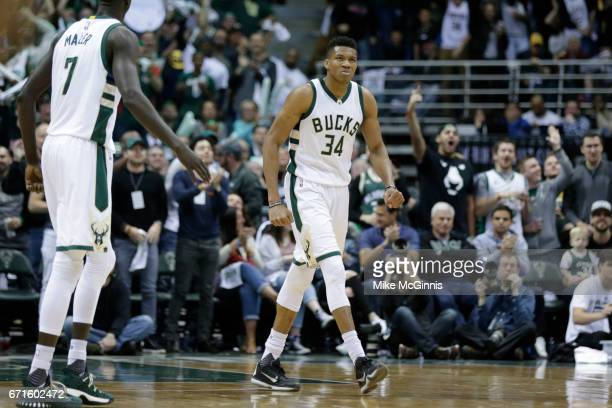 Giannis Antetokounmpo of the Milwaukee Bucks celebrates after driving to the hoop against DeMar DeRozan of the Toronto Raptors during the first half...