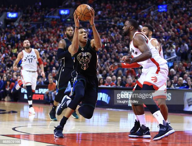 Giannis Antetokounmpo of the Milwaukee Bucks dribbles the ball as Patrick Patterson of the Toronto Raptors defends in the first half of Game One of...
