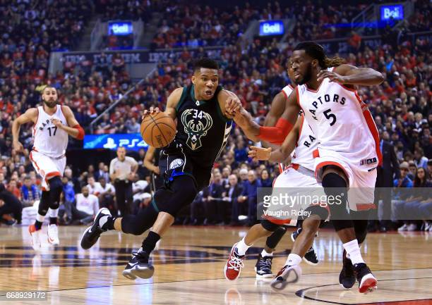 Giannis Antetokounmpo of the Milwaukee Bucks dribbles the ball as DeMarre Carroll of the Toronto Raptors defends in the first half of Game One of the...