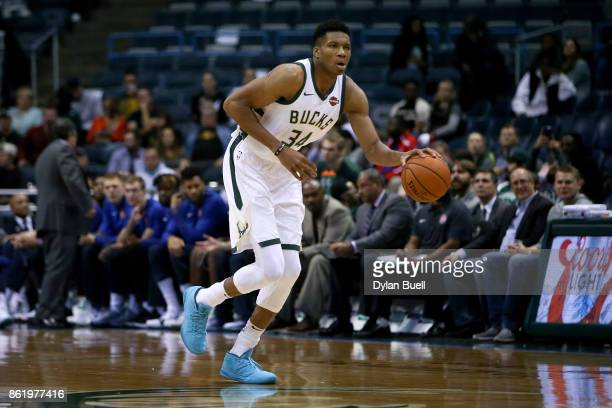 Giannis Antetokounmpo of the Milwaukee Bucks dribbles the ball in the first quarter against the Detroit Pistons during a preseason game at BMO Harris...