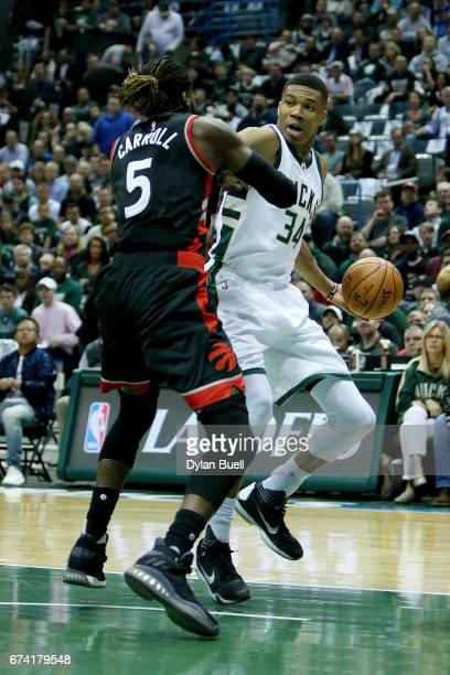 Giannis Antetokounmpo of the Milwaukee Bucks dribbles the ball while being guarded by DeMarre Carroll of the Toronto Raptors in the first quarter in...