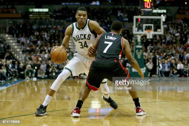 Giannis Antetokounmpo of the Milwaukee Bucks dribbles the ball while being guarded by Kyle Lowry of the Toronto Raptors in the second quarter in Game...
