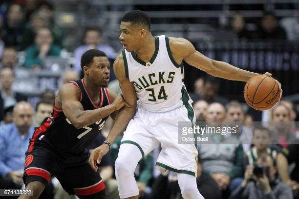 Giannis Antetokounmpo of the Milwaukee Bucks dribbles the ball while being guarded by Kyle Lowry of the Toronto Raptors in the fourth quarter in Game...