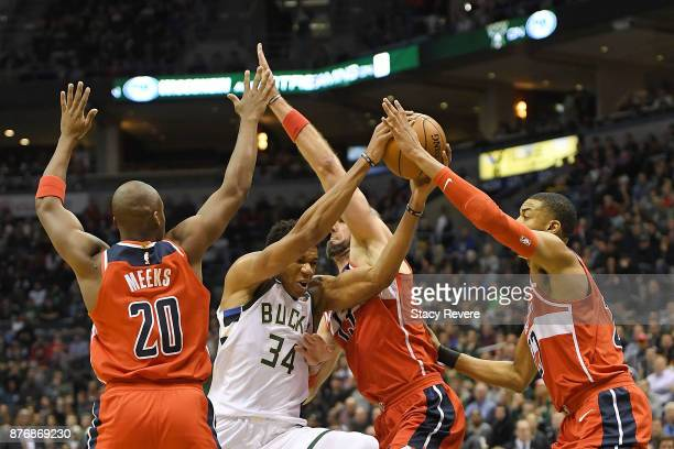 Giannis Antetokounmpo of the Milwaukee Bucks drives between Jodie Meeks and Marcin Gortat of the Washington Wizards during the first half of a game...