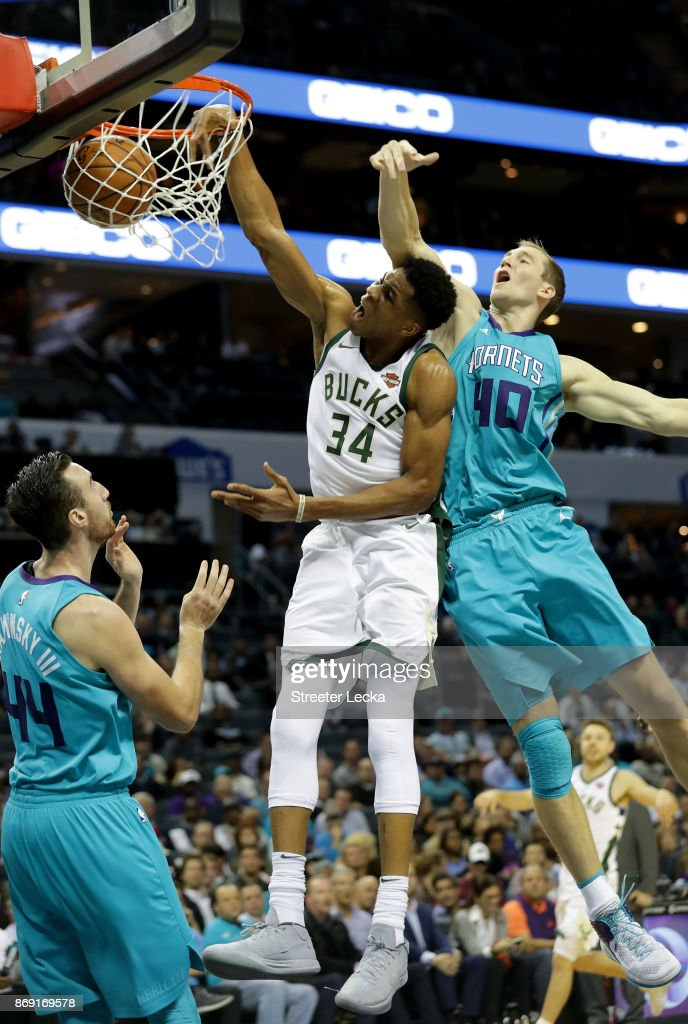 Giannis Antetokounmpo #34 of the Milwaukee Bucks dunks the ball against teammates Frank Kaminsky #44 and Cody Zeller #40 of the Charlotte Hornets during their game at Spectrum Center on November 1, 2017 in Charlotte, North Carolina.