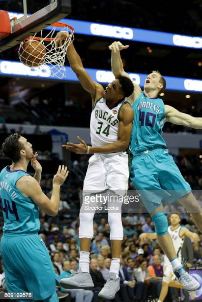Giannis Antetokounmpo of the Milwaukee Bucks dunks the ball against teammates Frank Kaminsky and Cody Zeller of the Charlotte Hornets during their...