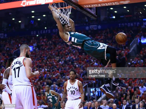 Giannis Antetokounmpo of the Milwaukee Bucks dunks the ball as Jonas Valanciunas of the Toronto Raptors looks on in the first half of Game Two of the...
