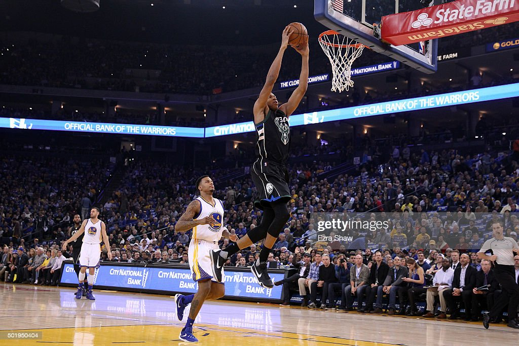 Giannis Antetokounmpo of the Milwaukee Bucks dunks the ball as Brandon Rush of the Golden State Warriors looks on at ORACLE Arena on December 18 2015...