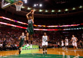 Giannis Antetokounmpo of the Milwaukee Bucks dunks the ball in front of Jordan Crawford of the Boston Celtics in the second half during the home...