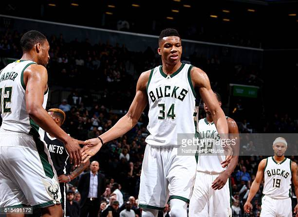 Giannis Antetokounmpo of the Milwaukee Bucks high fives teammates during the game against the Brooklyn Nets on March 13 2016 at Barclays Center in...