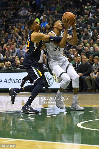 Giannis Antetokounmpo of the Milwaukee Bucks is fouled by Thabo Sefolosha of the Utah Jazz during a game at the Bradley Center on December 9 2017 in...