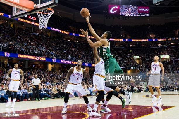 Giannis Antetokounmpo of the Milwaukee Bucks shoots over Iman Shumpert of the Cleveland Cavaliers and Tristan Thompson during the first half at...