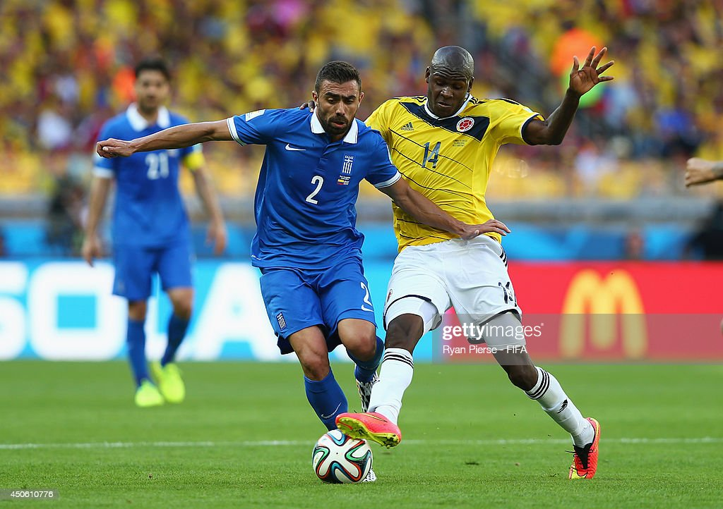 Giannis Maniatis of Greece (L) vies with Victor Ibarbo of Colombia during the 2014 FIFA World Cup Brazil Group C match between Colombia and Greece at Estadio Mineirao on June 14, 2014 in Belo Horizonte, Brazil.