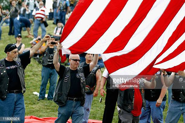 A giant American flag is hoisted by motorcyclists and Vietnam veterans from across the country as thye prepare to ride in the Rolling Thunder...