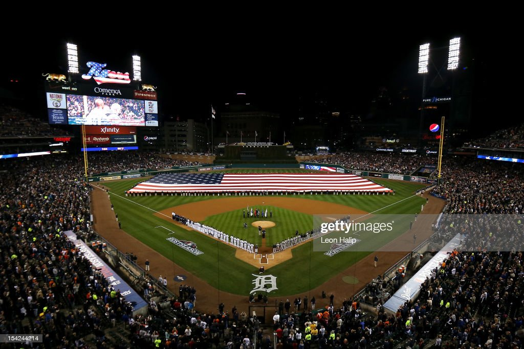 A giant American flag is spread across the field as players from the Detroit Tigers and the New York Yankees line up on the baseline during the performance of the National Anthem prior to game three of the American League Championship Series at Comerica Park on October 16, 2012 in Detroit, Michigan.