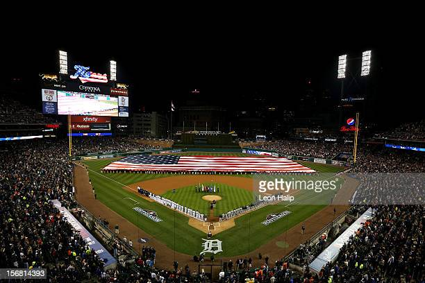 A giant American flag is spread across the field as players from the Detroit Tigers and the New York Yankees line up on the baseline during the...