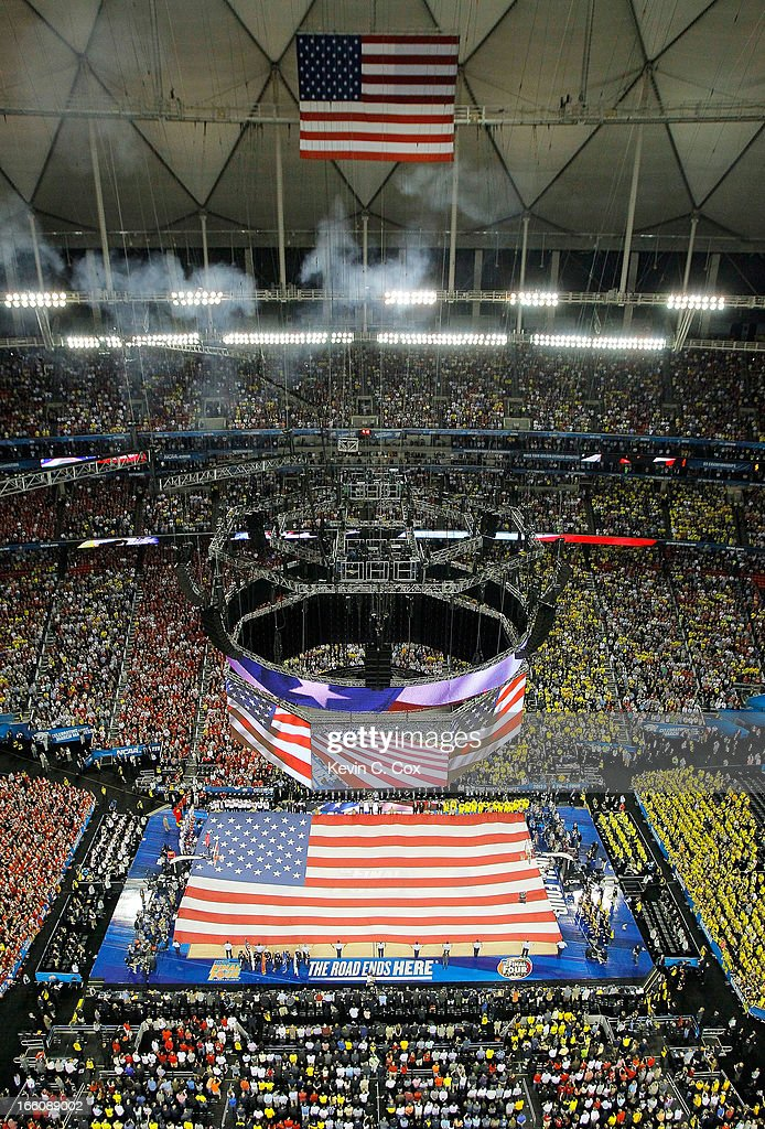 A giant American Flag is stretched across the court as singer Travis Tritt performs the National Anthem prior to the Louisville Cardinals playing...