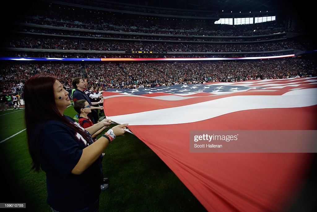 A giant American Flag is stretched across the field prior to the Houston Texans hosting the Cincinnati Bengals during their AFC Wild Card Playoff Game at Reliant Stadium on January 5, 2013 in Houston, Texas.