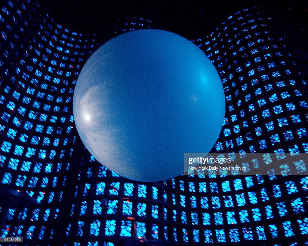 Giant ball hangs from ceiling against a backdrop of images on the wall at the New York Hall of Science in Flushing Meadows Park
