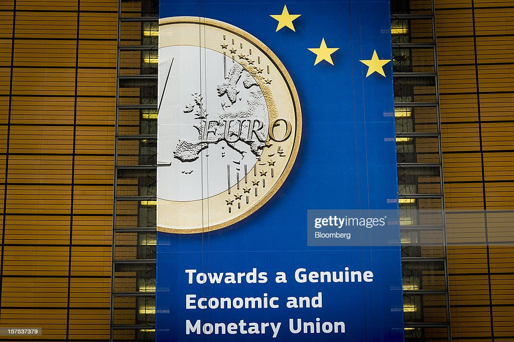 A giant banner promotes the euro currency and economic union on the exterior of the European Commission headquarterss in Brussels, Belgium, on Tuesday, Dec. 4, 2012. European finance ministers voiced confidence that Greece will pull off a successful bond buyback, the key element in a revamped effort to stem the debt crisis in the country where it started. Photographer: Jock Fistick/Bloomberg via Getty Images