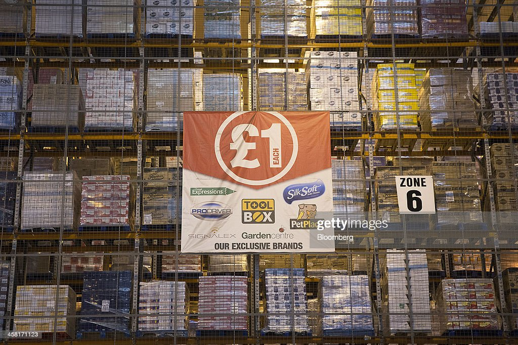 A giant banner, with a one pound symbol, hangs from a storage rack inside Poundland's goods distribution warehouse, operated by Poundland Holdings Ltd.,in Bilston, U.K., on Friday, Dec. 20, 2013. U.K. discount retailer Poundland has hired Rothschild to manage its IPO, according to the Sunday Times newspaper. Photographer: Simon Dawson/Bloomberg via Getty Images