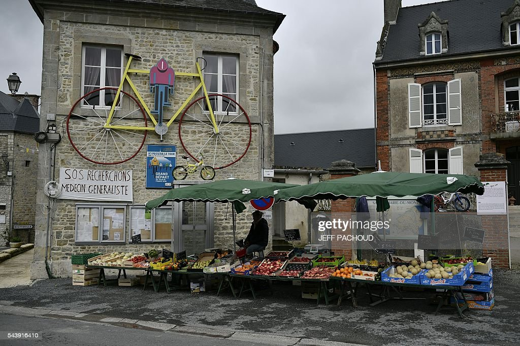 A giant bike is installed on the facade of a building in Sainte-Marie-du-Mont, Normandy, on July 30, 2016, two days before the start of the 103rd edition of the Tour de France cycling race. The 2016 Tour de France will start on July 2 in the streets of Le Mont-Saint-Michel and ends on July 24, 2016 down the Champs-Elysees in Paris. / AFP / jeff pachoud